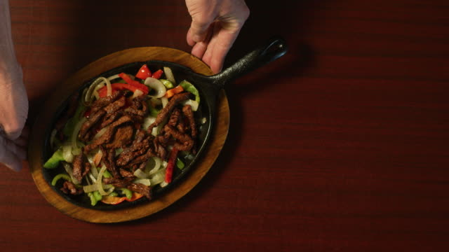 directly overhead shot of a person placing a plate of steaming beef fajitas and vegetables on a table - arranging stock videos and b-roll footage