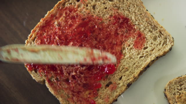 directly overhead shot of a six year-old caucasian boy using a kitchen knife to scoop jelly from the jar and then spreading it on to a piece of bread sitting on a plate while making a peanut butter and jelly sandwich at a kitchen table indoors - making a sandwich stock videos and b-roll footage