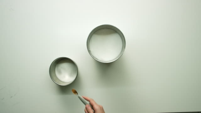 Directly Overhead Shot of a Woman's Hand Using a Measuring Spoon of Cinnamon into a Bowl of Sugar on a White Table