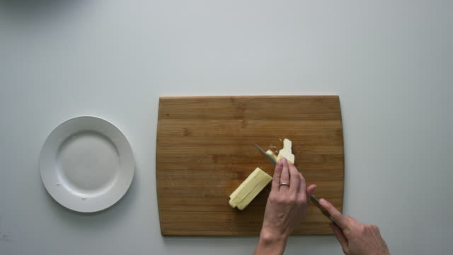 directly overhead shot of a woman's hands cutting a stick of butter into small pieces on a wooden cutting board on a white surface - butter stock videos & royalty-free footage