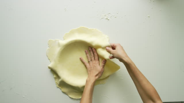 directly overhead shot of a woman's hands forming a sheet of flat pastry dough to the inside of a pie dish in preparation for filling - pastry dough stock videos & royalty-free footage