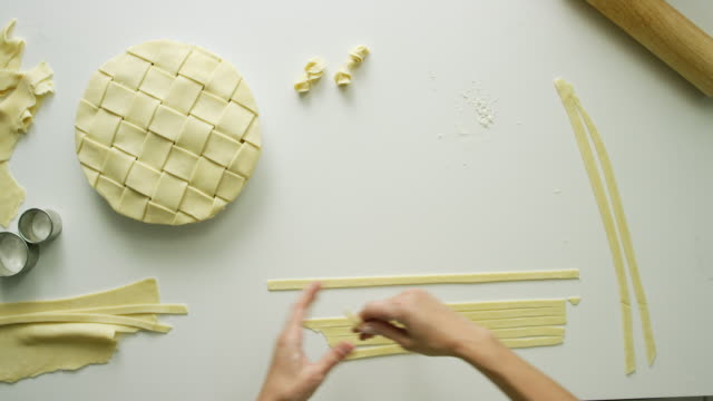 directly overhead shot of a woman's hands picking up strips of pastry dough up off a table in preparation for braiding them for a lattice pie decoration - organic stock videos & royalty-free footage