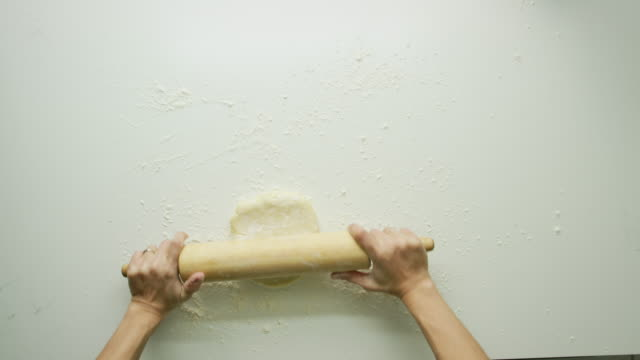 directly overhead shot of a woman's hands rolling out a large sheet of pastry dough with a wooden rolling pin and turning it over on a white table - dough stock videos & royalty-free footage