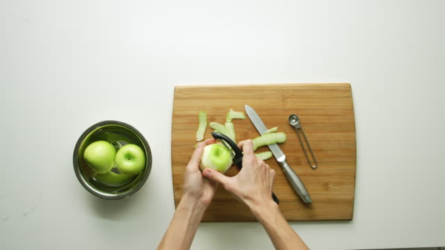 directly overhead shot of a woman's hands setting a small bowl of green apples on to a white table and then peeling them with a vegetable peeler over a wooden cutting board - peeling food stock videos & royalty-free footage