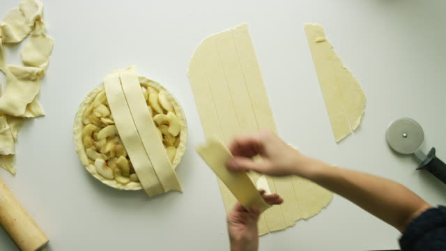 directly overhead shot of a woman's hands weaving strips of pastry crust dough together to form a lattice pie top crust on an apple pie - organic stock videos & royalty-free footage