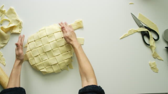 directly overhead shot of a woman's hands weaving strips of pastry dough together to form a lattice pie top crust then trimming the edges with scissors - pastry dough stock videos & royalty-free footage