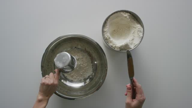 vidéos et rushes de prise de vue directement au-dessus des mains d'une jeune femme ramasser une tasse à mesurer, écopant de farine un boîtier, à l'aide d'un couteau de cuisine pour enlever l'excès par le haut et verser dans un bol à mélanger sur un tableau blan - savoir faire
