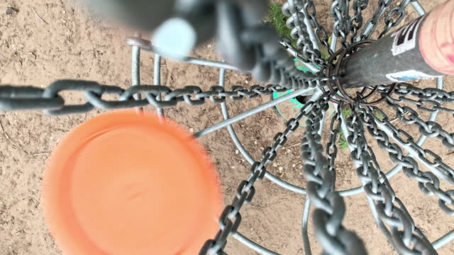 directly overhead shot of an orange disc golf driver hitting the chains of a disc golf basket with great speed at a disc golf course (frisbee golf) - holing stock videos & royalty-free footage