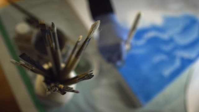 directly overhead shot of paintbrushes in a glass container in the foreground and an artist wearing protective gloves painting on a canvas in the background - artist stock videos & royalty-free footage