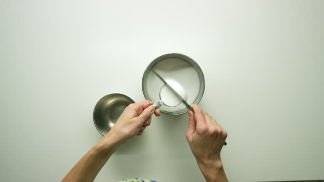 Directly Overhead Shot of Young Woman's Hands Using a Measuring Cut to Scoop Sugar from a Canister, Using a Knife to Level It, and then Pouring It Into a Smaller Metal Bowl on a White Table