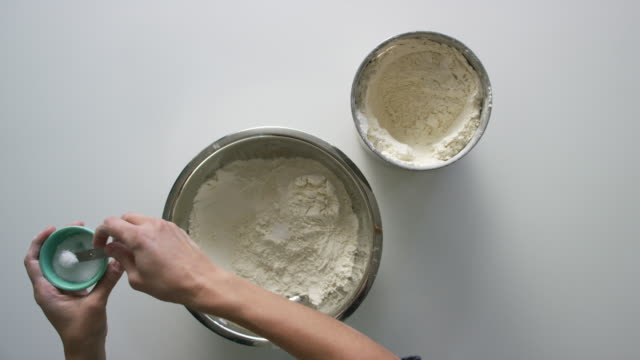 directly overhead shot of young woman's hands using a measuring spoon to scoop salt from a small bowl and pouring it into a mixing bowl with flour in it on a white table - dough stock videos & royalty-free footage