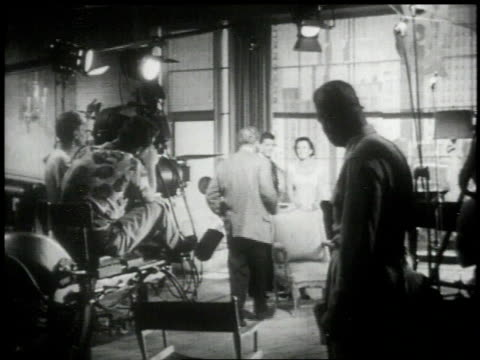 vídeos de stock e filmes b-roll de 1951 ws director coaching actors prior to filming a scene - montagem de filme estúdio de cinema