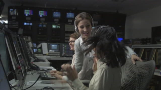 ms director congratulating two businesswomen in television studio control room / culver city, california, usa - sala di controllo video stock e b–roll