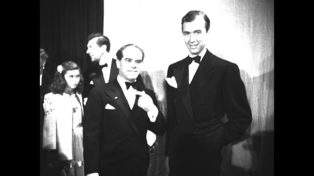 director frank capra stands with actor jimmy stewart inside the shrine auditorium in los angeles as they attend the 19th academy awards ceremony - フランク キャプラ点の映像素材/bロール