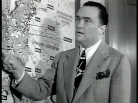 stockvideo's en b-roll-footage met director j edgar hoover standing talking to agent at wall map of usa ms hoover talking vs cu 'wanted german saboteur' posters printing from machine... - 1942