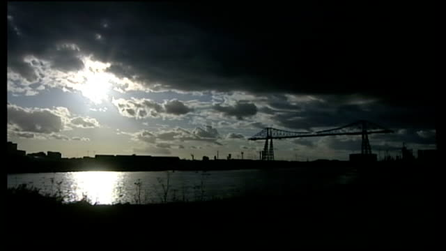 Teesside Transporter bridge and river in silhouette against dark sky Smoking industrial chimneys