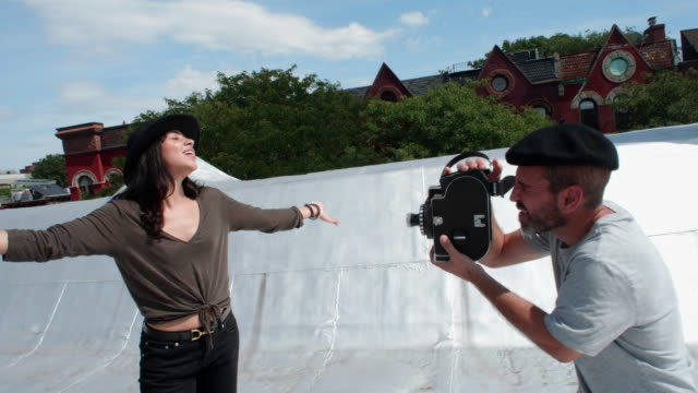 director winds old film camera then films beautiful actress posing on city rooftop - film director stock videos & royalty-free footage