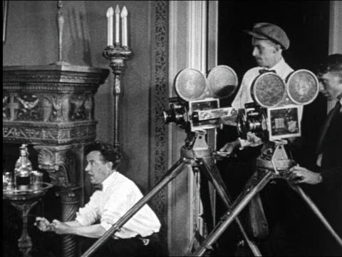 B/W 1922 director working with 2 cameramen in studio / documentary