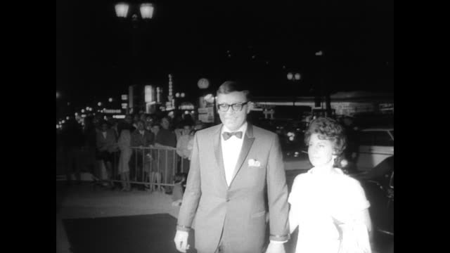 ext director's guild theater in hollywood / cu playbill for movie 'rosie' / star rosalind russell arrives at theater with producer jacques mapes /... - nancy sinatra stock videos and b-roll footage