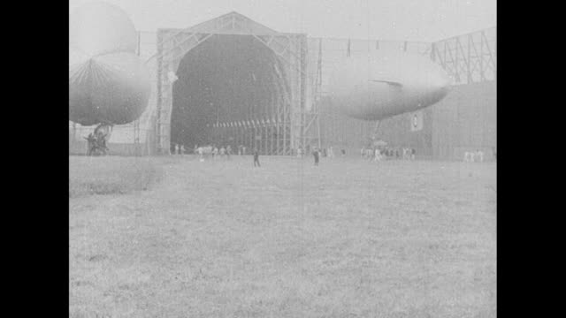 ls dirigible airship taxis out of hangar / ms ground crew watch as airship lifts off / ls airship flies overhead / ls airship flies over boats and... - airship stock videos & royalty-free footage