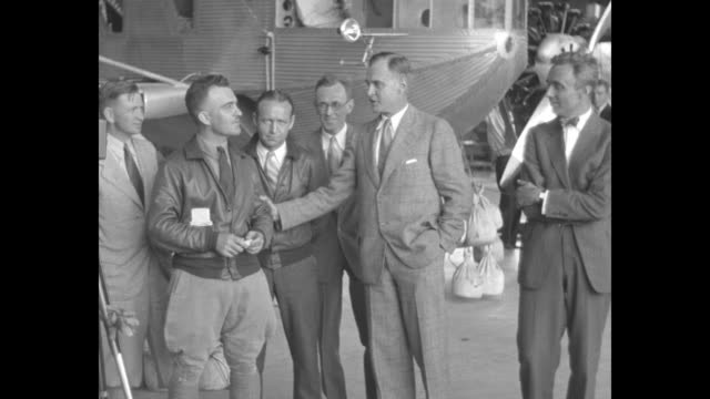 ZMC2 dirigible in hangar / man climbs tall ladder against shiny side of airship / Navy Captain William E Kepner talks with others and speaks into...