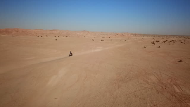 a dirt bike rider races through the empty desert and back to camp. - survival stock videos and b-roll footage