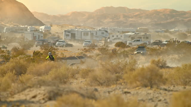 dirt bike rider racing across desert terrain near encampment of motor homes and rvs near the salton sea - wilderness stock videos & royalty-free footage
