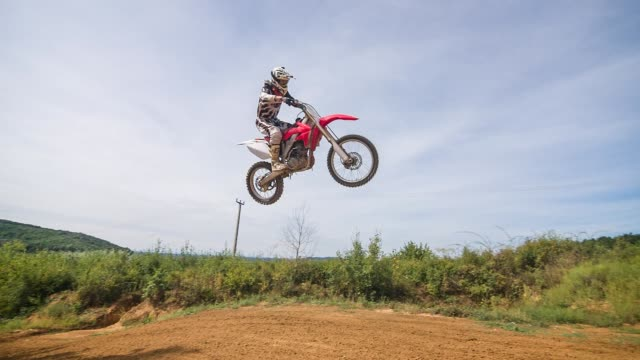 dirt biker jumping on dirt track while off road racing, slow motion - off road racing stock videos & royalty-free footage