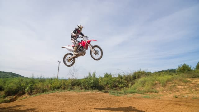 dirt biker jumping on dirt track while off road racing - off road racing stock videos & royalty-free footage