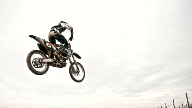 SLO MO Dirt biker jumping over dirt ramp