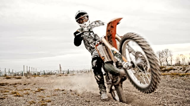 SLO MO Dirt biker riding fast through rutted turn
