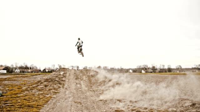 slo mo dirt biker riding through the turn - motocross video stock e b–roll