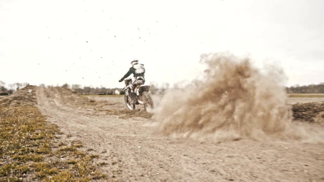 SLO MO Dirt biker speeding through the turn