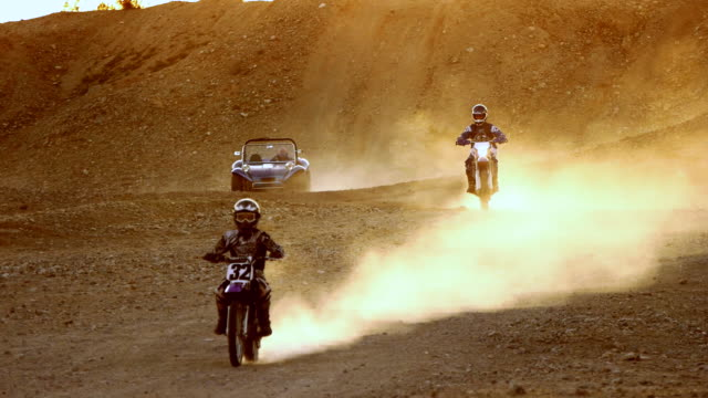 ws td dirt bikers and dune buggy riding through desert at sunset kicking up big clouds of dust and dirt / salton city, california, usa - dune buggy stock videos and b-roll footage