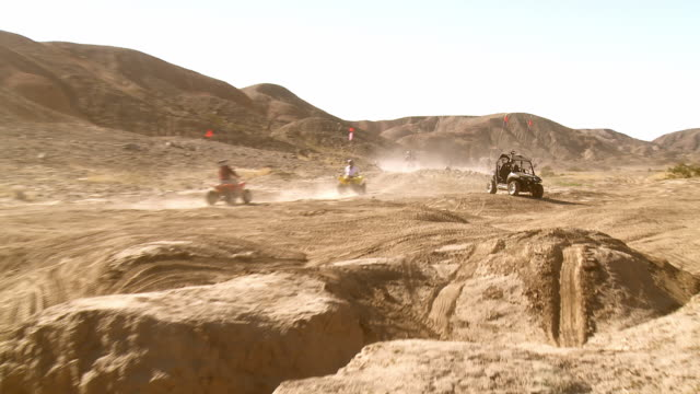 dirt bikers and weekend rock crawlers in jeeps have fun in a desert recreation area in california. - querfeldeinrennen stock-videos und b-roll-filmmaterial