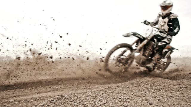 slo mo dirt bikers riding fast through the turn - strada in terra battuta video stock e b–roll