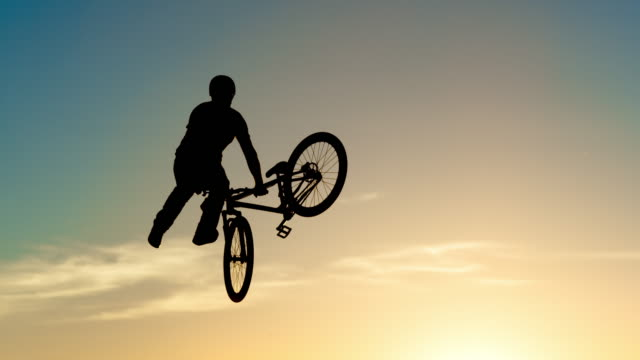 slo mo dirt jump biker silhouette doing a trick at sunset - jumping stock videos & royalty-free footage