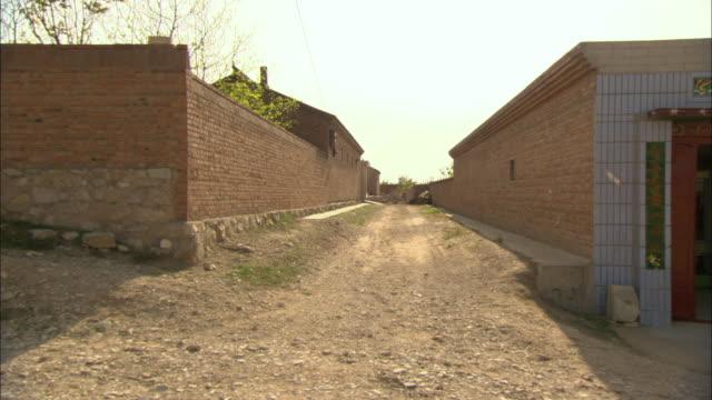 WS PAN Dirt road and brick buildings in village, Longbaoshan Village, Hebei, China