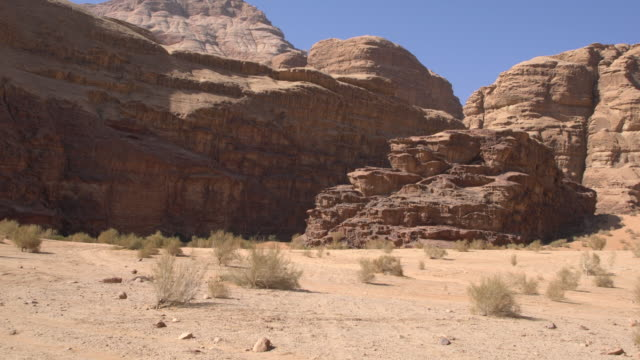 A dirt road and dramatic sandstone mountains in Wadi Rum Desert, Jordan