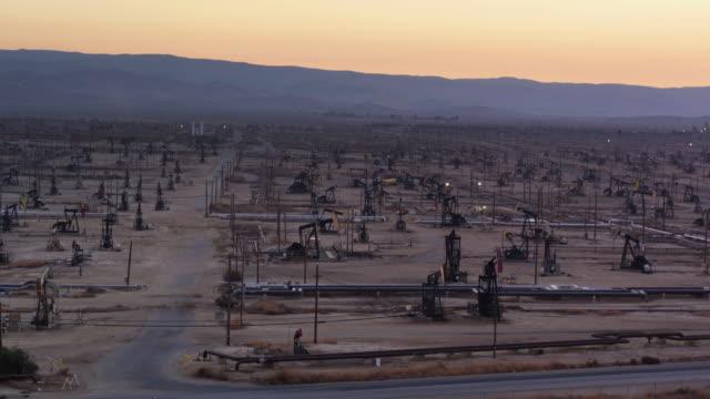 dirt road between pump jacks in south belridge oil field in kern county, california at dusk - drone shot - trivella petrolifera video stock e b–roll