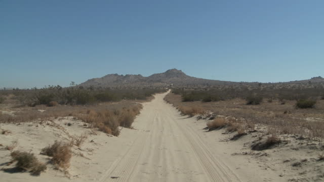 WS POV Dirt road in desert, rugged mountain in background / Palmdale, California, USA