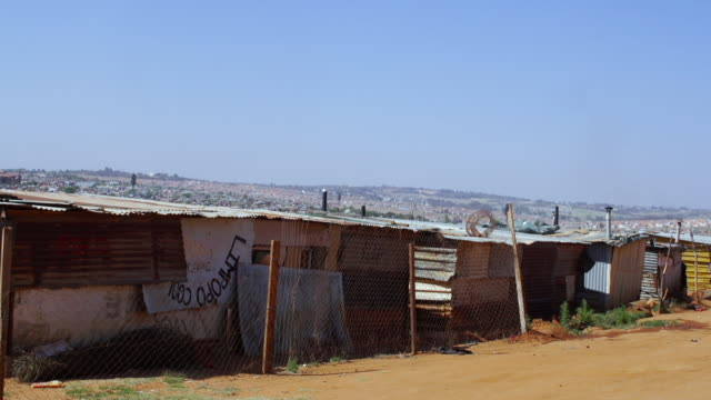 WS Dirt road in township lined with wire fences and shacks / Cosmo City, South Africa