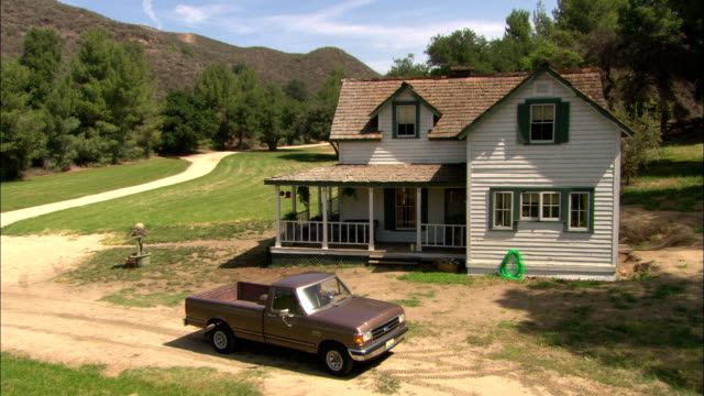 a dirt road leads to a driveway with a pickup parked in front of a house with a wrap-around porch. - zweistöckiges wohnhaus stock-videos und b-roll-filmmaterial