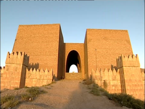vídeos de stock e filmes b-roll de a dirt road leads to the arched entrance of the masqah gate. - iraque