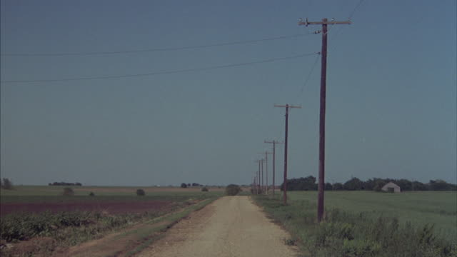 a dirt road lined with telephone poles runs through farmland in the countryside. - telegraph pole stock videos and b-roll footage