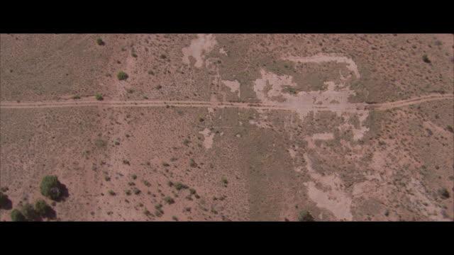 vídeos y material grabado en eventos de stock de aerial view, circling, dirt road on flat landscape - formato buzón