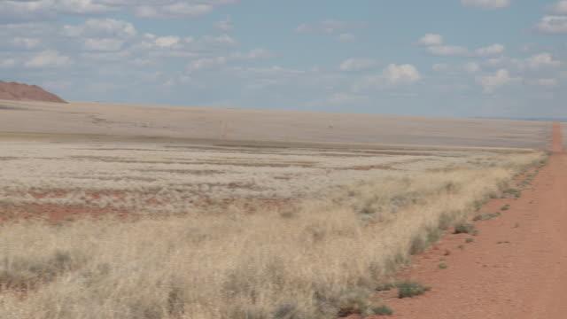vídeos y material grabado en eventos de stock de a dirt road runs through the namibian desert. - desierto del kalahari
