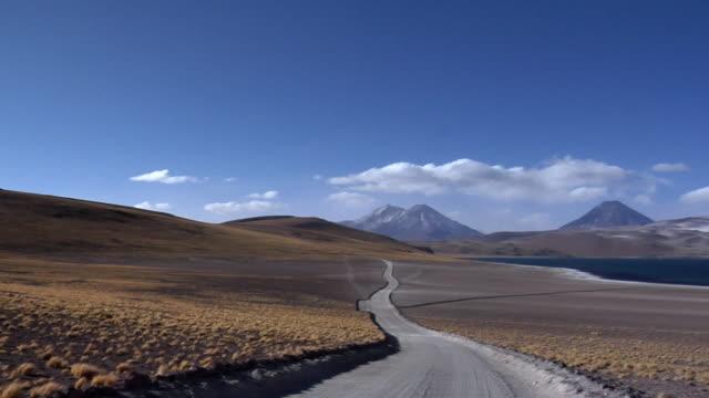 ws pan dirt road with volcanoes and lake in desert landscape, san pedro de atacama, el loa, chile - san pedro de atacama stock videos & royalty-free footage