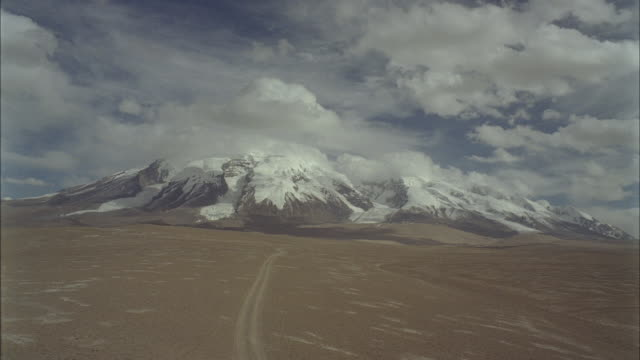a dirt track across barren desert leads to distant snow-covered mountains. - remote location stock videos & royalty-free footage