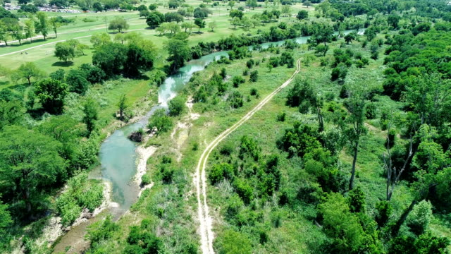 dirt trail and blanco river winding across green texas landscape in san marcos , texas , usa - strada in terra battuta video stock e b–roll